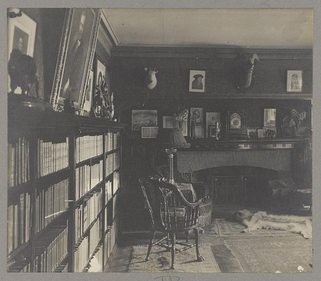 interior of Roosevelt's library at Sagamore Hill with a bookcase, hearth and mantle, several photographs, sculpture, mounted antelope heads, a badger skin rug and other carpeting, and chairs. 1905